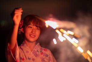 花火を掲げる浴衣姿の若い女性の写真素材 [FYI03813712]