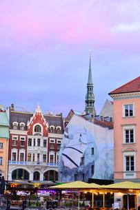 ラトビア・首都リガ旧市街世界遺産の歴史地区にある聖ペテロ教会の尖塔と明かりで飾られたテラス席の景観の写真素材 [FYI03814239]