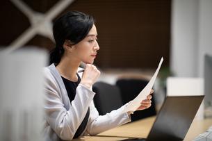 書類を見て考えるビジネス女性の写真素材 [FYI03814424]