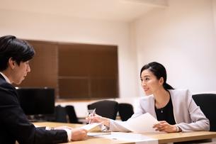 対面で打ち合わせするビジネス男女の写真素材 [FYI03814427]