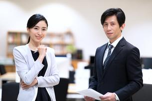 カメラ目線で微笑むビジネス男女の写真素材 [FYI03814435]