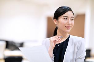 書類を持って横を見るビジネス女性の写真素材 [FYI03814445]