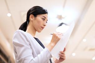 書類を持って考えるビジネス女性の写真素材 [FYI03814447]