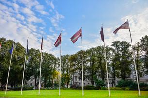 ラトビア・首都リガ旧市街世界遺産の歴史地区の芝生に並ぶラトビアの国旗の写真素材 [FYI03814661]