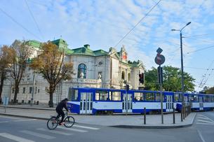 ラトビア・首都リガ旧市街にあるラトビア国立劇場の前を走るトラムと自転車の写真素材 [FYI03814670]