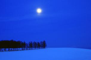 夜の雪原と満月の写真素材 [FYI03814947]