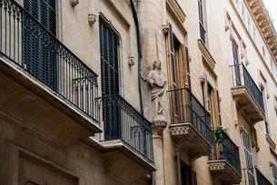 天使の彫刻とベランダ:マヨルカ島・パルマ旧市街の路地の写真素材 [FYI03815050]