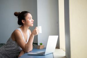 ノートパソコンを広げて遠くを見ている女性の写真素材 [FYI03815607]