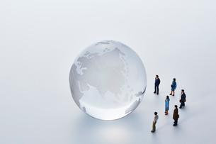 地球儀のまわりを囲むミニチュアの人々の写真素材 [FYI03815740]