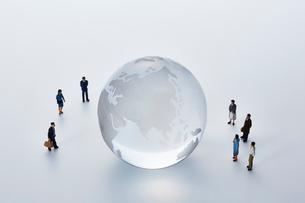 地球儀のまわりを囲むミニチュアの人々の写真素材 [FYI03815741]