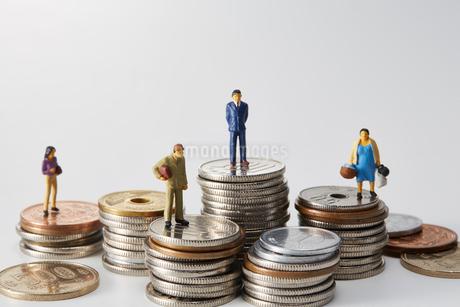 積み重ねられた日本の硬貨の上に立つミニチュアの人々の写真素材 [FYI03815759]