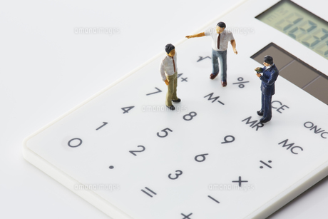 電卓の上に立つミニチュアの人の写真素材 [FYI03815769]