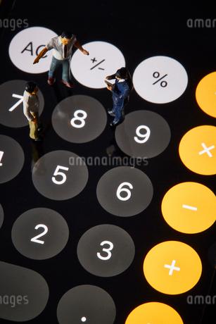 電卓の上に立つミニチュアの人の写真素材 [FYI03815771]