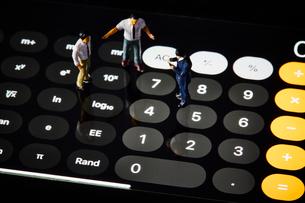 電卓の上に立つミニチュアの人の写真素材 [FYI03815772]
