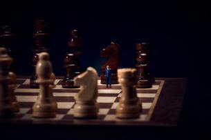 チェスのボードの上に置かれた駒とスーツを着たミニチュア人形の写真素材 [FYI03815787]