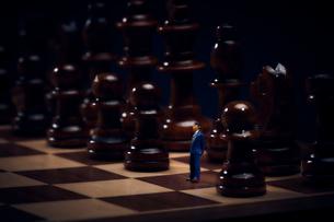 チェスのボードの上に置かれた駒とスーツを着たミニチュア人形の写真素材 [FYI03815788]