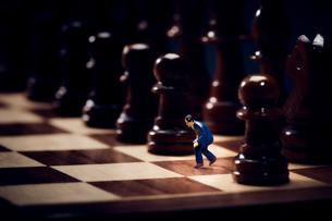チェスのボードの上に置かれた駒とスーツを着たミニチュア人形の写真素材 [FYI03815789]