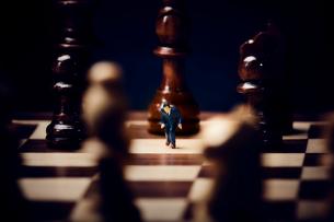 チェスのボードの上に置かれた駒とスーツを着たミニチュア人形の写真素材 [FYI03815790]