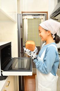 キッチンでパンを焼く女の子の写真素材 [FYI03815821]