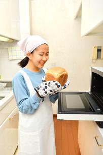 キッチンでパンを焼く女の子の写真素材 [FYI03815822]
