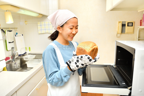 キッチンでパンを焼く女の子の写真素材 [FYI03815823]