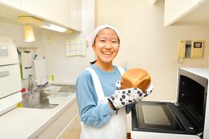 キッチンでパンを焼く女の子の写真素材 [FYI03815824]