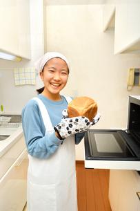 キッチンでパンを焼く女の子の写真素材 [FYI03815825]