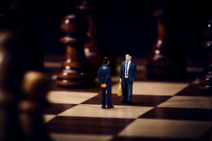 チェスのボードの上のスーツを着た向かい合うミニチュア人形の写真素材 [FYI03815864]