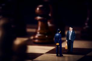チェスのボードの上のスーツを着た向かい合うミニチュア人形の写真素材 [FYI03815865]
