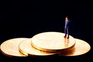 コインの上のスーツを着た男性のミニチュア人形の写真素材 [FYI03815871]