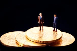 コインの上のスーツを着た男性のミニチュア人形の写真素材 [FYI03815872]