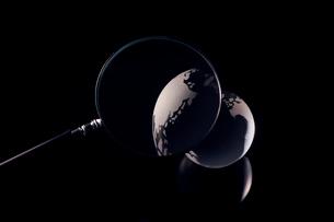暗闇のガラス製の地球を拡大する虫眼鏡の写真素材 [FYI03815873]