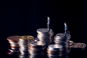 積み上げられた複数の日本のお金と働く人のミニチュアの写真素材 [FYI03815879]
