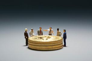 コインを囲むミニチュア人形の写真素材 [FYI03815896]