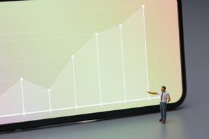 スマートフォンに表示されたグラフとミニチュア人形の写真素材 [FYI03815898]