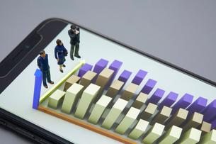 スマートフォンに表示されたグラフとミニチュア人形の写真素材 [FYI03815900]