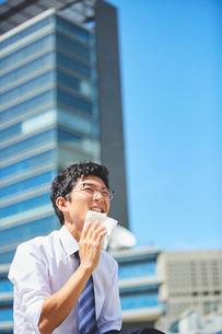炎天下でハンカチで汗を拭うサラリーマンの写真素材 [FYI03815946]