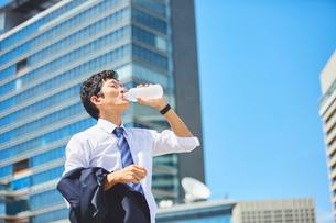 炎天下で水分補給をするサラリーマンの写真素材 [FYI03815952]