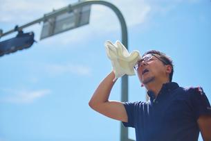 炎天下でタオルで汗を拭う作業員の写真素材 [FYI03815957]