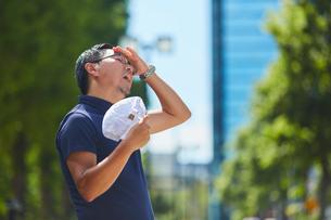 炎天下で防止で風を扇ぐ作業員の写真素材 [FYI03815959]