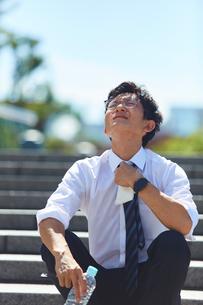 炎天下の暑さにネクタイを緩めるサラリーマンの写真素材 [FYI03815961]