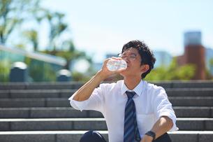 炎天下で水分補給をするサラリーマンの写真素材 [FYI03815963]