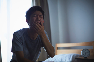 熱帯夜で寝付けず寝不足の男性の写真素材 [FYI03815974]