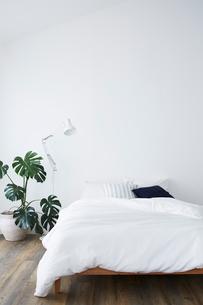 白い壁とフローリングの部屋に置かれたベッドの写真素材 [FYI03815985]