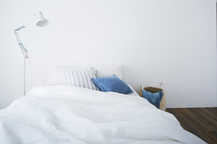 白い壁とフローリングの部屋に置かれたベッドの写真素材 [FYI03815986]