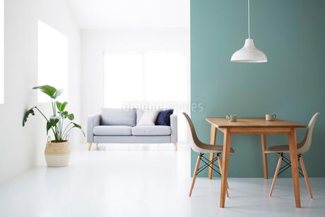 白い空間の中にあるグレーのソファとダイニングセットの写真素材 [FYI03815996]