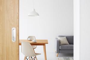 白い壁と白い床の空間にあるダイニングセットとベッドの写真素材 [FYI03816003]