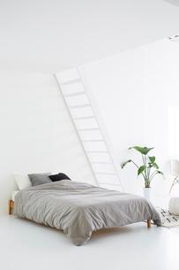 白い壁と白い床の空間にあるベッドルームの写真素材 [FYI03816005]