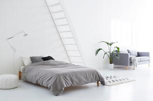 白い壁と白い床の空間にあるベッドルームの写真素材 [FYI03816006]