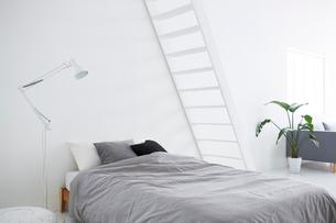 白い壁と白い床の空間にあるベッドルームの写真素材 [FYI03816007]